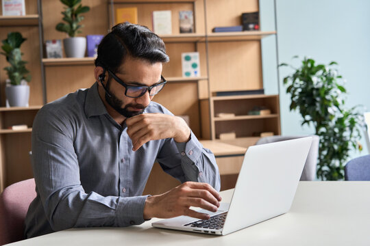 Latin indian serious businessman wearing glasses and headset having virtual team meeting call, remotely working at home watching online learning training webinar in remote office.
