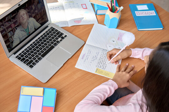 Indian cute kid school girl having virtual online English language class with male tutor teacher sitting at table at home. Over shoulder top view of latin student learning writing in notebook.