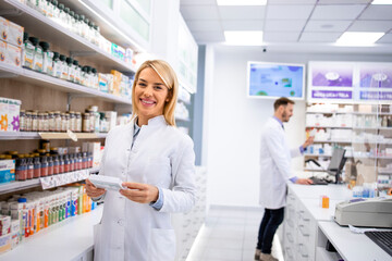 Portrait of beautiful female pharmacist standing in pharmacy store by the shelf with medicines.