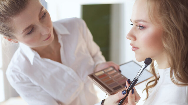 beautiful young model woman getting fashion make-up