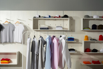 Pastel white, gray, blue and pink cotton sportswear on a rail in the store. Clothes at custom clothing printing company