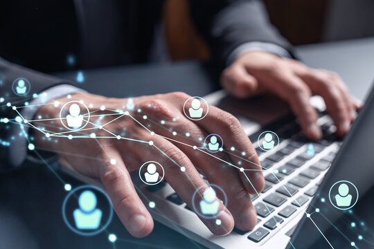 Hands of hr specialist is typing the keyboard in the internet to find the best candidates to create international network in recruitment process. Formal wear. Social media hologram icons.