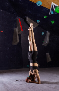Athletic young woman  practicing yoga in indoor climbing gym, doing headstand (Sirsasana)