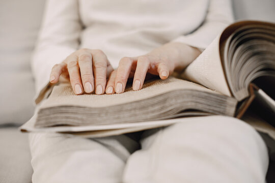 Mature woman read braille book on couch