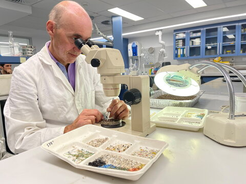 Australian Microplastic Assessment Project Research Director Dr Scott Wilson looks at microplastics through a microscope at Macquarie University in Sydney