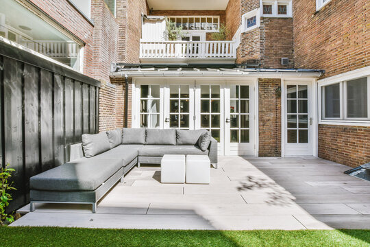 Contemporary comfortable sofa placed in backyard outside house with brick walls on sunny summer day