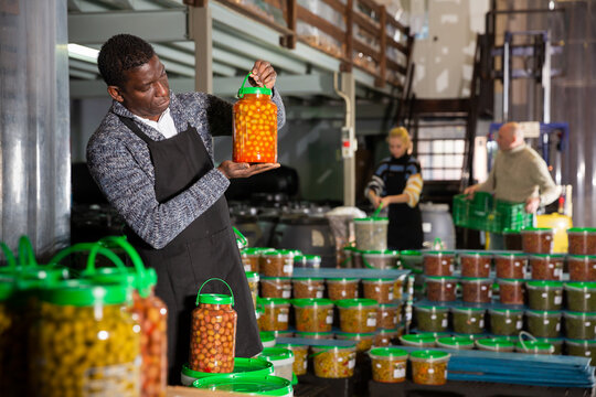 Focused African-American man working in food producing factory, inspecting and arranging glass jar with pickled olives
