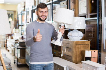 Fototapeta Young man satisfied with purchase of stylish table lamp in furniture store