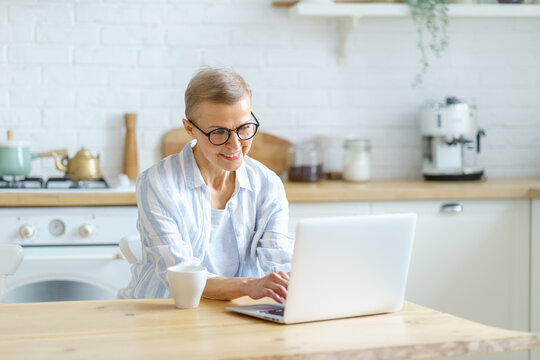 Modern happy mature woman wearing glasses working or studying on laptop while sitting in kitchen at home looking at screen and typing something on keyboard. Senior people and technologies concept