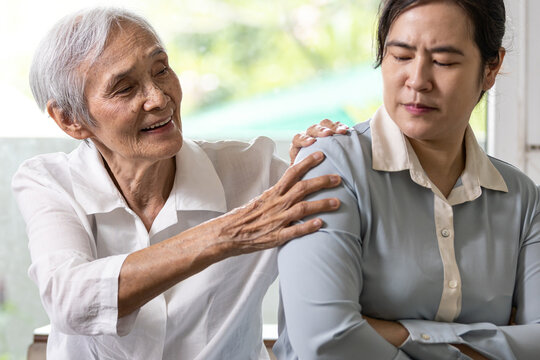 Asian senior grandmother reconcile touchy her granddaughter,angry upset woman with crossed arms,old elderly trying to reconcile by shoulder squeeze after conflict,misunderstanding,family life problems