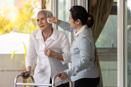 Asian caregiver wiping the sweat on face of the old elderly by tissue paper,assist help clean sweat on skin face,take care of old elderly in hot summer weather on a sunny day,high temperature at home.