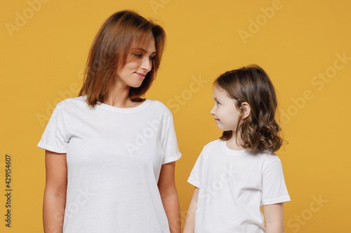 Happy woman in white t-shirt have fun with cute child baby girl 5-6 years old look to each other. Mommy little kid daughter isolated on yellow orange color background Mother's Day love family concept