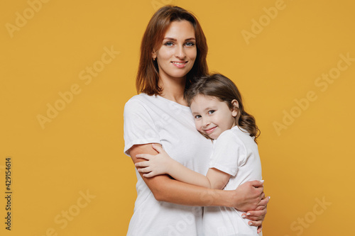 Happy woman in basic white t-shirt have fun with cute child baby girl 5-6 years old hugs. Mommy little kid daughter isolated on yellow orange color background studio. Mother's Day love family concept.
