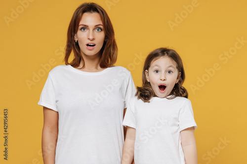 Happy amazed woman in basic white t-shirt have fun with cute child baby girl 5-6 years old. Mom little kid daughter isolated on yellow orange color background studio. Mother's Day love family concept.