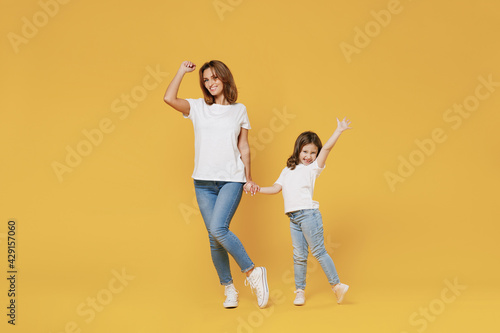 Full length happy woman in basic white t-shirt have fun with cute child baby girl 5-6 years old hold hands. Mom little kid daughter isolated on yellow color background studio Mother's Day love family