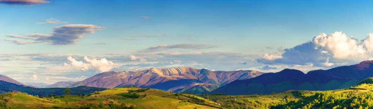 mountainous rural panorama landscape in springtime. beautiful scenery beneath a sky with clouds. grass covered hill rolling in to the distant ridge