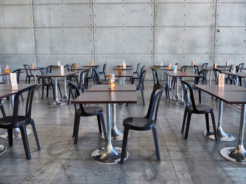 Empty school cafeteria with small square tables and plastic chairs