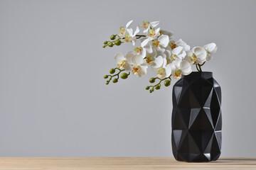 Obraz Modern black vase with orchid flower on gray background. - fototapety do salonu