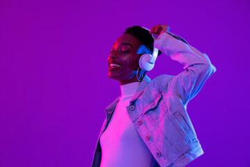Young African American woman wearing headphones listening to music and dancing in futuristic purple...
