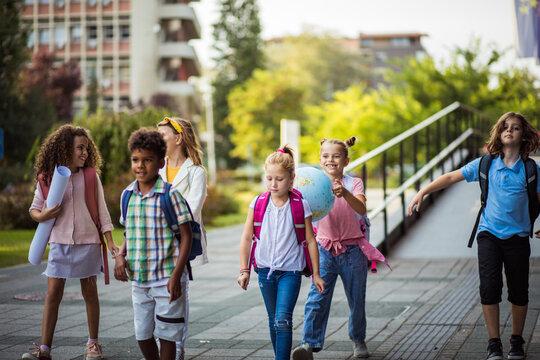 School kids walking in schoolyard.