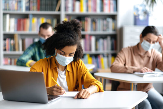 Learning during a pandemic. Students in protective medical masks sit in the university library at a distance from each other. African american female student taking notes during lecture