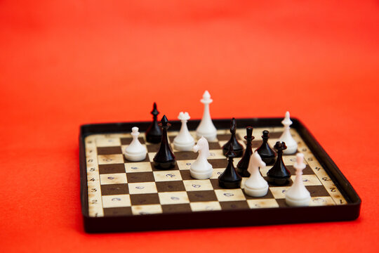 Travel magnetic chess board with chess pieces on a red background. Chess game white vs black pawns