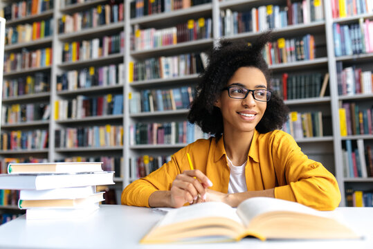 Teenage african american female pretty student with glasses, studying while sits at the table in a college library, reads books to searching information for a lesson or exam, doing homework,looks away