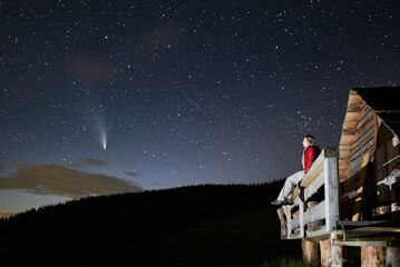 Fototapeta Female traveler sitting on wooden plank and looking at majestic night sky with stars and comet Neowise. Young woman hiker enjoying fantastic view of blue starry sky while resting outside forest house.