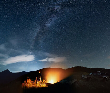 Silhouette of man standing next to logs watching campfire in the mountains under starry sky with Milky way. Offroad truck, mountain peak on background.
