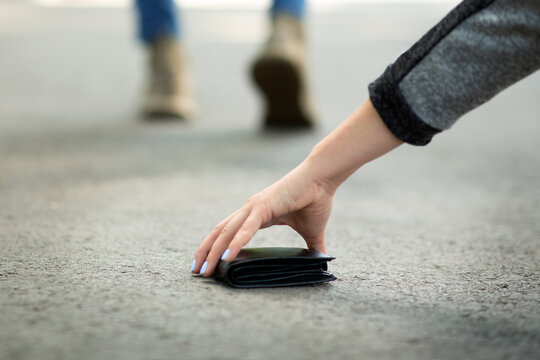 Close up view of young woman picking up lost wallet on city street, empty space