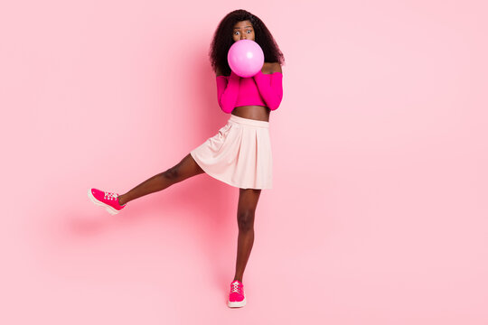 Photo of lady raise leg blow balloon wear top unclothed shoulders mini skirt sneakers isolated pink color background