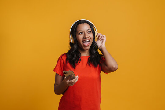 Black young woman listening music with cellphone and headphones