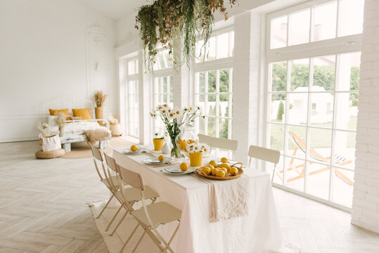 Beautifully served spring summer white table with lots of lemons and chamomile.