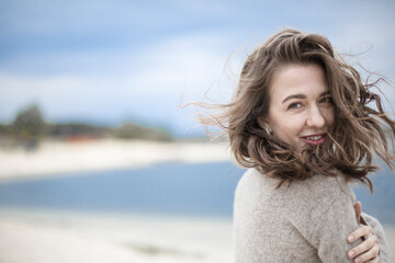 Fototapeta portrait of a beautiful sensual young woman, hair develops the wind, brunette with emotions, hands hair and face, seaside wind outside