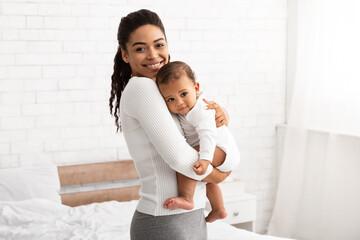 African American Mommy Carrying Little Baby Standing In Bedroom Indoor
