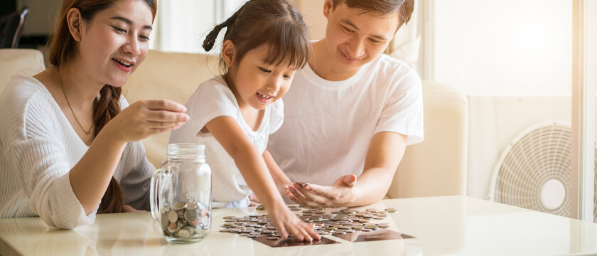 Banner photo of Asian family teach their daughter to saving money and putting coins into glass bank spend a quality time together. Asian family, relationship, happiness and investment concept