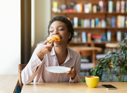 Pretty black woman enjoying breakfast at cafe, eating fresh croissant and drinking aromatic coffee