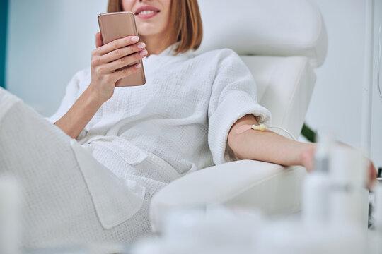 Beautiful Caucasian woman sitting in armchair during medicine procedure in spa salon
