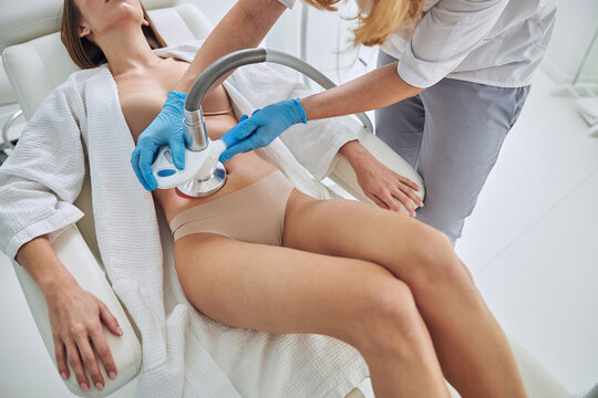 Unrecognized woman in white bathrobe receiving Ultrasound cavitation body contouring treatment in wellness clinic