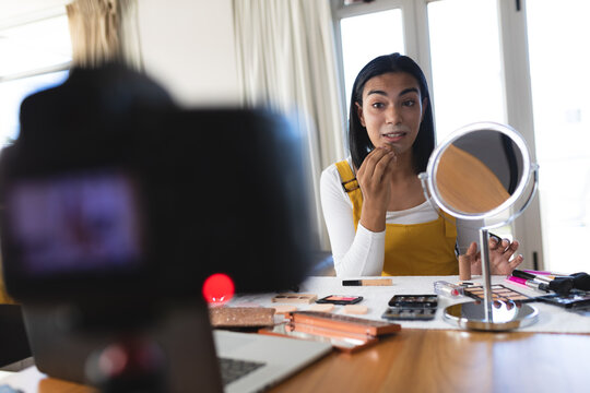 Mixed race transgender woman making vlog using laptop and camera putting on makeup