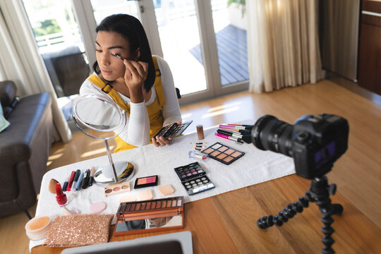 Happy mixed race transgender woman making vlog using laptop and camera putting on makeup