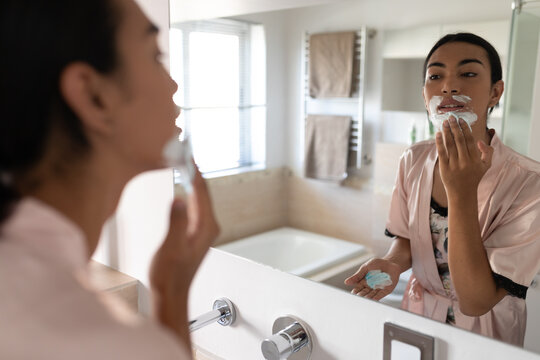 Mixed race transgender woman looking in bathroom mirror and putting on shaving cream