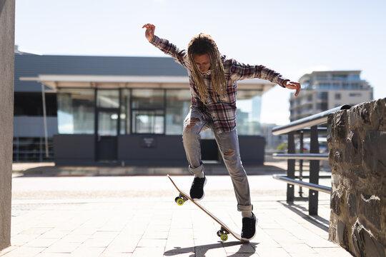 Mixed race male with dreadlocks skateboarding in the street
