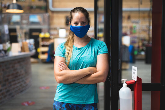 Portrait of caucasian woman wearing mask standing in corridor at gym