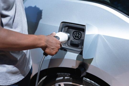 Close up of man charging electric car