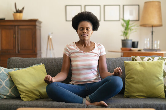 Smiling african american woman sitting on sofa, meditating at home