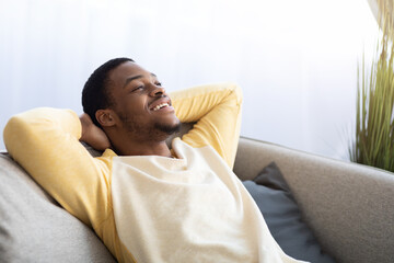 Obraz Closeup of black guy relaxing on couch at home - fototapety do salonu
