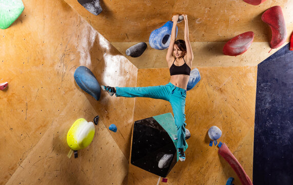 Caucasian young woman bouldering in indoor climbing gym