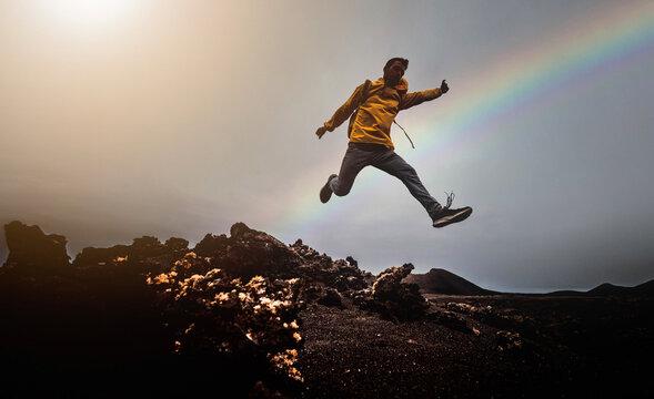 Man jump through the gap over the mountain rocks at sunset