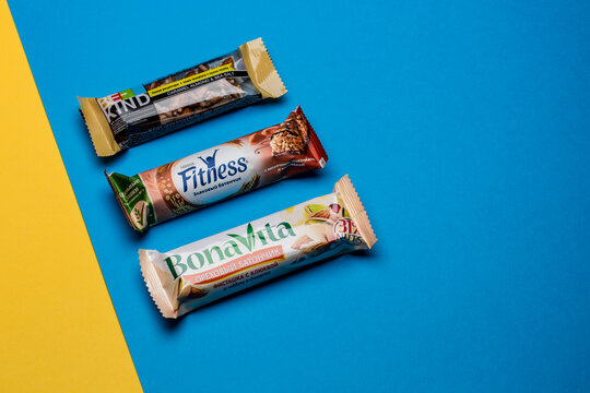 Moscow, Russia - April 20 2021: Three protein bars on blue and yellow paper background.